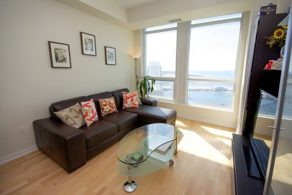 Living Area With Gleaming Hardwood Flooring Throughout Facing Stunning Unobstructed Lake Views.
