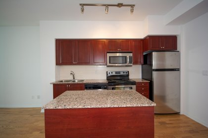 Designer Kitchen Cabinetry With Stainless Steel Appliances, Granite Counter Tops, Centre Island & Gleaming Hardwood Flooring.