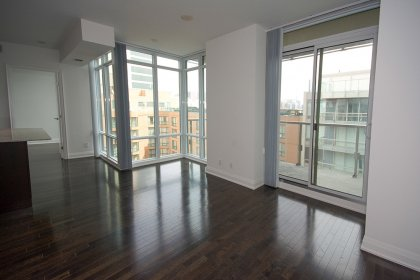 Bright Wrap Around Floor-To-Ceiling Windows With Gleaming Hardwood Flooring.
