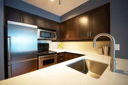 Designer Kitchen Cabinetry With Stainless Steel Appliances, Quartz Counter Tops, Undermount Sink & A Breakfast Bar.