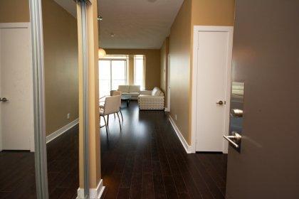Suite Foyer With Mirrored Closet & Laminate Flooring.