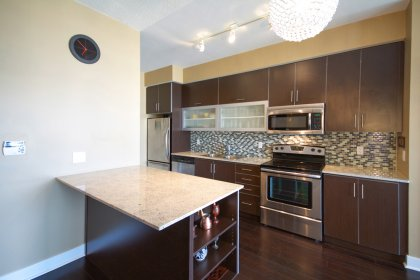 Gorgeous Designer Kitchen Cabinetry With Stainless Steel Appliances, Granite Counter Tops, Glass Tile Backsplash, A Centre Breakfast Bar / Island With