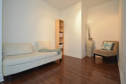 Open Concept Den Are With Gleaming Hardwood Flooring.