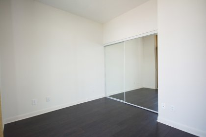 Spacious Sized Master Bedroom With Mirrored Closets & A Walk-Out Balcony Facing C.N. Tower Views.