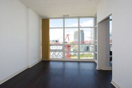 Living & Dining Area With Bright Floor-To-Ceiling Windows And Hardwood Flooring Throughout Facing Balcony C.N. Tower Views.
