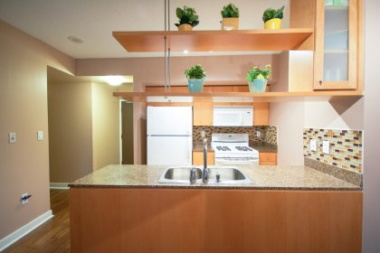 Designer Kitchen Cabinetry With Granite Counter Tops & A Glass Tile Backsplash.
