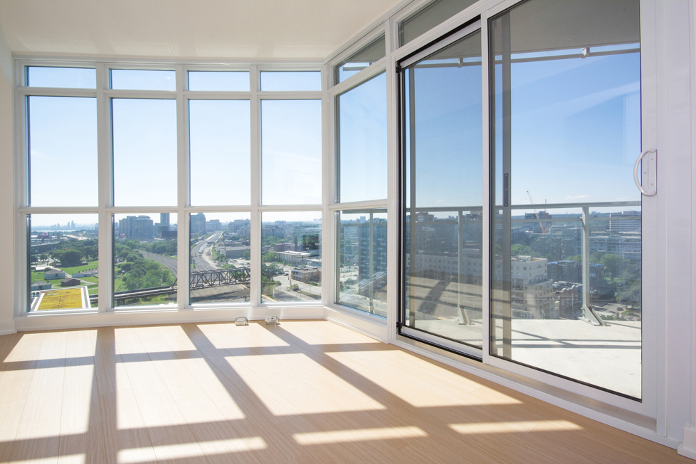 Bright Floor To Ceiling Windows With Laminate Flooring Facing Unobstructed  City Views.