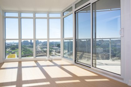 Bright Floor-To-Ceiling Windows With Laminate Flooring Facing Unobstructed City Views.