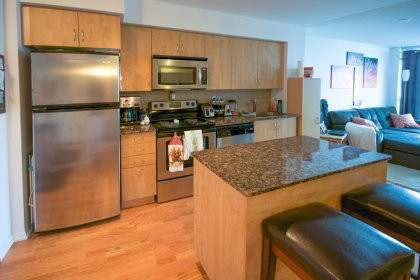 Designer Kitchen Cabinetry With Stainless Steel Appliances, Granite Counter Tops, Centre Island & Hardwood Flooring.