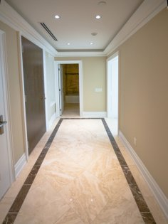 Suite Foyer With Marble Flooring Coffered Ceiling, Crown Moulding & Pot Lighting.