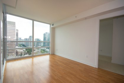 Bright Floor-To-Ceiling Windows With Laminate Flooring Facing Unobstructed South Views.