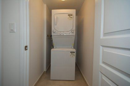 Laundry Area With Stacked Washer/Dryer & Ensuite Storage Space.