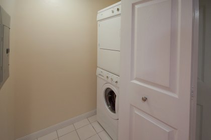 Laundery With Ample Storage & A Stacked Washer / Dryer.