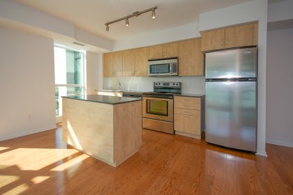 Designer Kitchen Cabinetry With Stainless Steel Appliances, Granite Counter Tops & A Centre Island.