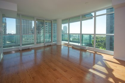 Bright Floor-To-Ceiling Wrap Around Windows With Hardwood Flooring Facing Park & Lake Views.