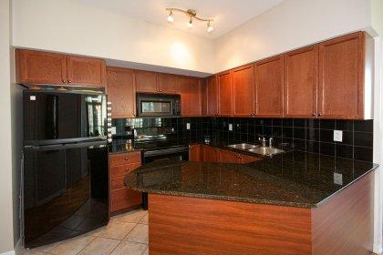 Designer Kitchen Cabinetry With Granite Counter Tops & A Ceramic Backsplash.