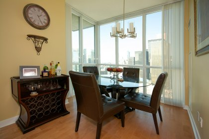 Bright Floor-To-Ceiling Windows With Laminate Flooring Throughout Facing City Views.