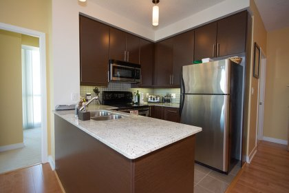Designer Kitchen Cabinetry With Stainless Steel Appliances, Granite Counter Tops, Undermount Sink With Valance Lighting & A Breakfast Bar.