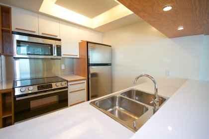 Designer Kitchen Cabinetry With Stainless Steel Appliances & A Breakfast Bar.