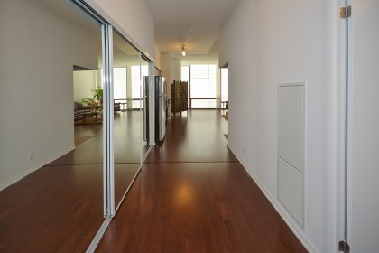Suite Foyer With Mirrored Closets & Hardwood Flooring.