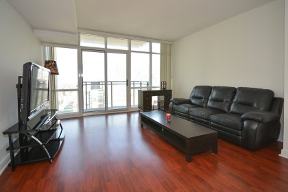 Bright Floor-To-Ceiling Windows With Laminate Flooring Throughout & Balcony C.N. Tower Views.