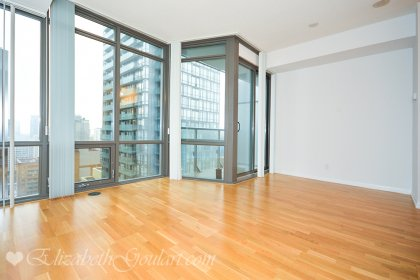 Open Concept Living / Dining Areas With Floor-To-Ceiling Windows & Hardwood Flooring.