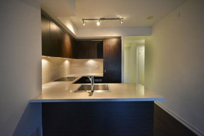 Designer Kitchen Cabinetry With Stainless Steel Appliances, Undermount Sink, Stone Backsplash & Counter Tops With A Breakfast Bar & Laminate Flooring.