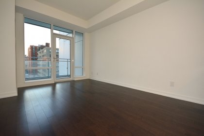 Bright Floor-To-Ceiling Windows With Laminate Flooring Throughout & A Large Walk-Out Balcony Facing Unobstructed Views.
