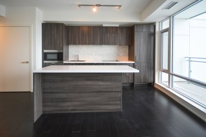 Designer Kitchen Cabinetry With Stainless Steel Appliances, Undermount Sink, Stone Backsplash & Counter Tops With A Breakfast Bar & Hardwood Flooring.