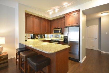 Gorgeous Designer Kitchen Cabinetry With Stainless Steel Appliances, Granite Counter Tops, An Undermount Sink, Valance Lighting & Mirrored Backsplash.