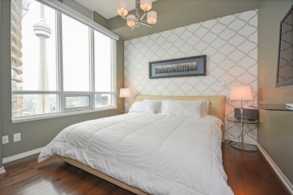 Spacious Sized Bedroom With Designer Wall Paper, Hardwood Flooring Throughout Facing C.N. Tower Views.