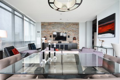 Open Concept Living & Dining Areas With Hardwood Flooring Throughout. A Custom Stone Accent Wall Including A Built-In Wall Unit.