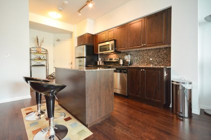Designer Kitchen Cabinetry With Stainless Steel Appliances, Granite Counter Tops With Backsplash & A Breakfast Bar.