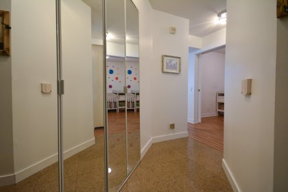 Suite Foyer With Mirrored Closets & Granite Flooring.