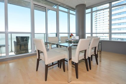 Bright Dining Area With Wrap Around Windows And Hardwood Flooring Facing Stunning South Unobstructed Lake & Island Views.