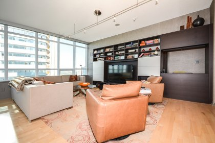 Bright Living & Dining Areas With Wrap Around Windows, Hardwood Flooring, A Custom Built-In Wall Unit & Reconfigured Study Area.