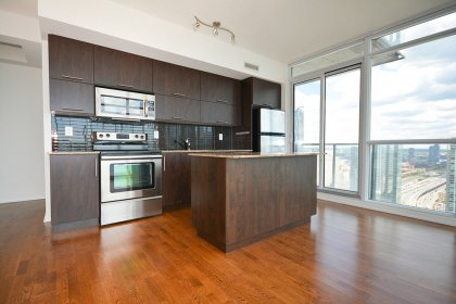 Designer Kitchen Cabinetry With Stainless Steel Appliances, Granite Counter Tops, An Undermount Sink, A Breakfast Bar & Hardwood Flooring.