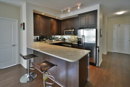 Gorgeous Designer Kitchen Cabinetry With Stainless Steel Appliances, Granite Counter Tops, An Undermount Sink With Valance Lighting & A Breakfast Bar.