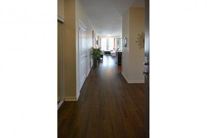 Suite Foyer With Mirrored Sliding Doors & Hardwood Flooring.