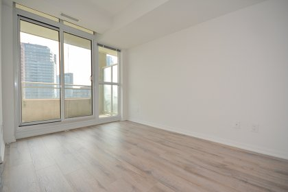 Master Bedroom With A Large Closet, Laminate Hardwood Flooring Throughout & A Walk-Out To The Balcony.