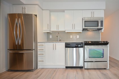 Designer Kitchen Cabinetry With Stainless Steel Appliances, Granite Counter Tops, An Undermount Sink & Laminate Hardwood Flooring Throughout.