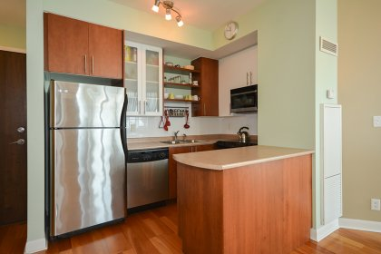 Designer Kitchen Cabinetry With Stainless Steel Appliances & A Custom Breakfast Bar.