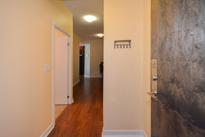 Suite Foyer With Mirrored Closets & Laminate Flooring Throughout.