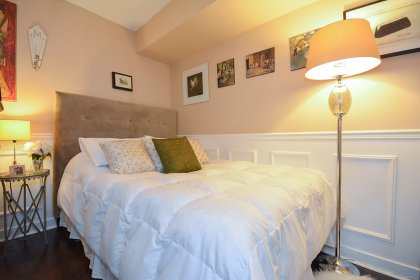 Spacious Sized Master Bedroom With A Customized Door, Wainscoting & Hardwood Flooring Throughout.