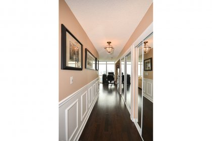 Suite Foyer With Mirrored Closets, Wainscoting & Hardwood Flooring Throughout.