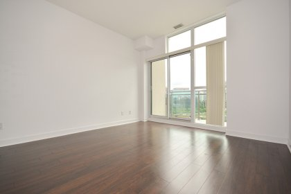 Bright Floor-To-Ceiling Windows With Laminate Flooring & A Walk-Out Balcony.