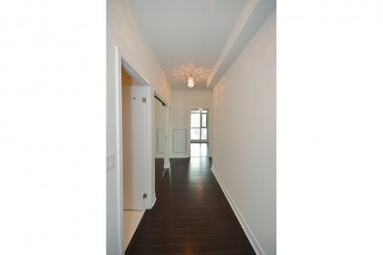 Suite Foyer With A Large Mirrored Closet & Hardwood Flooring.