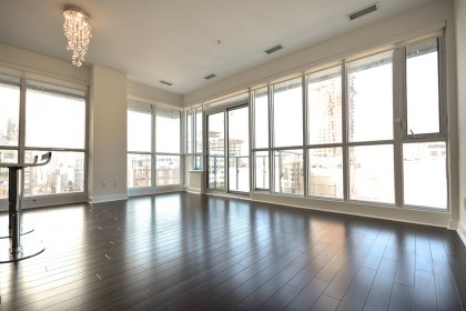 Bright Floor-To-Ceiling Wrap Around Windows With Laminate Flooring Throughout.