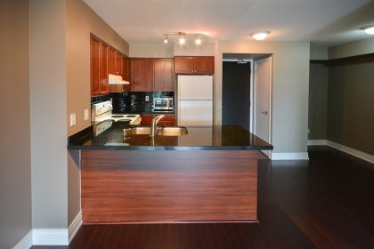 Designer Kitchen Cabinetry With Granite Counter Tops, An Undermount Sink & A Breakfast Bar.