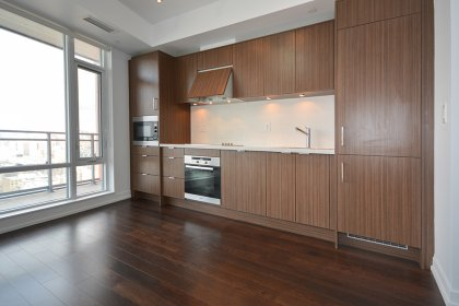 Designer Kitchen Cabinetry With Stainless Steel Appliances, Stone Counter Top & Hardwood Flooring Throughout.